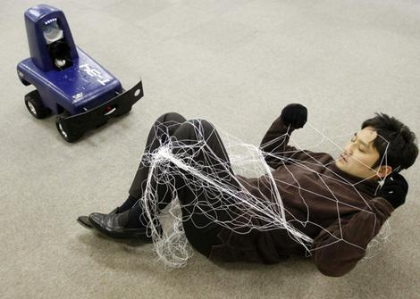 A mock intruder, tangled in a net that was launched by the remote-controlled security robot T-34, lies on the floor in Tokyo